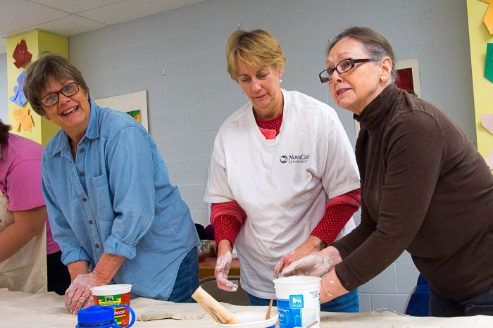 Artist Hilda Eiber works with class participants during the Introduction to Pottery and Handbuilding class.