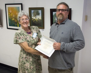 "Berkeley Arts Council president Malinda Shaver presents the ""Best in Show"" certificate to Neil Super."