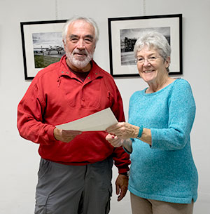 "Arts Council president Malinda Shaver presents the Best in Show Award to Bruce Chandler for his painting ""Coastal Rocks"""