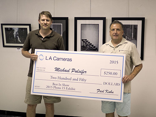 Mike Pulsifer accepts a presentation check from Fred Kuhn of LA Cameras of Chambersburg, PA, who sponsored the Best in Show prize.