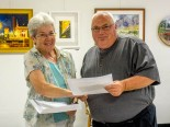 "Arts Council President Malinda Shaver presents Merit Award to Joe Goodrich at the ""Heavy Metal"" reception on September 9"