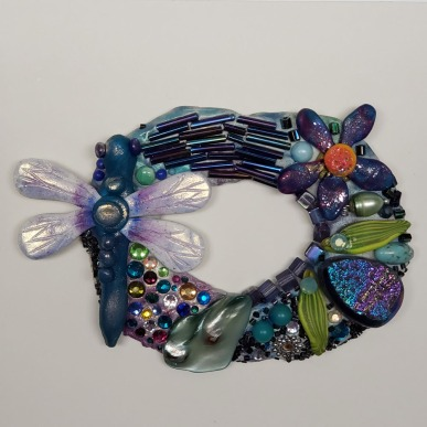 Oval wall hanging with dragonfly